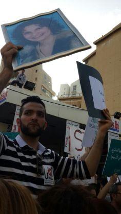 KAFA activist holds image of a Domestic violence victim. Taken by Alina Razzouk
